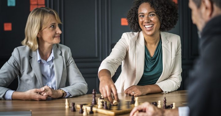 female and male co-workers playing chess