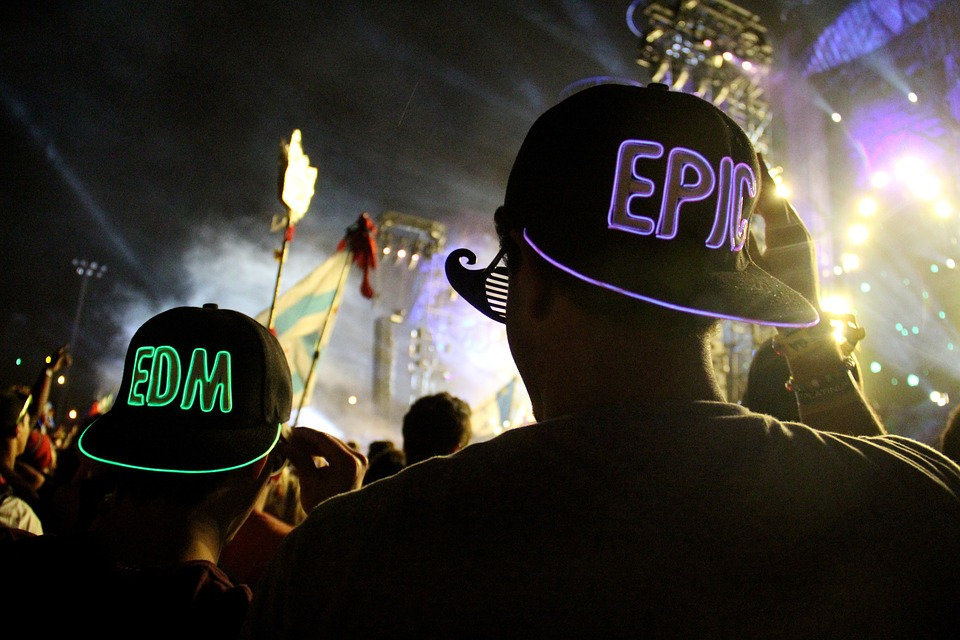 Neon hats being worn in a crowd with letters EDM and word EPIC on the back