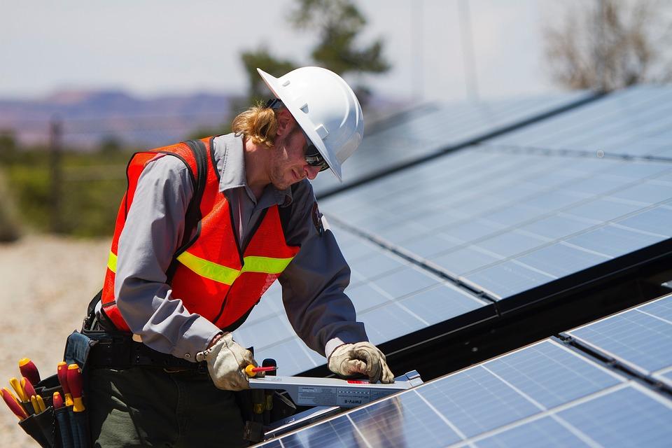 guy installing solar panels on roof