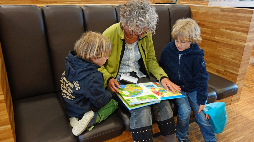 grandma reading books to two kids