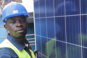 Man posing with solar panels and wearing a hardhat